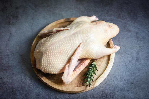Anatra cruda con spezie alle erbe pronte da cucinare, carne fresca di anatra sul vassoio in legno per alimenti, anatra intera