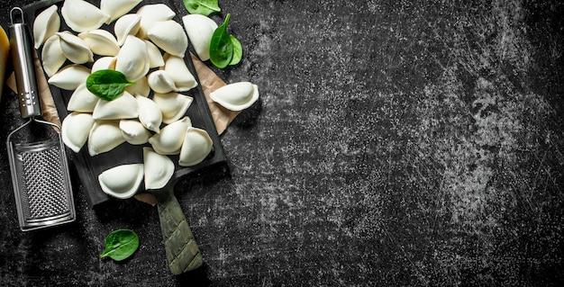 Gnocco crudo. cucinare gnocchi fatti in casa con patate sul tavolo rustico scuro