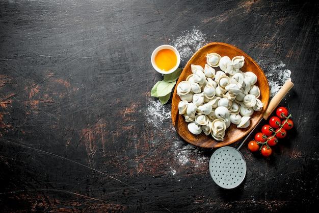 Gnocco crudo sulla piastra con tuorlo d'uovo e pomodorini sul tavolo rustico
