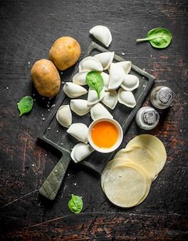 Gnocco crudo. gnocchi di preparazione con patate e spezie sul tavolo rustico scuro