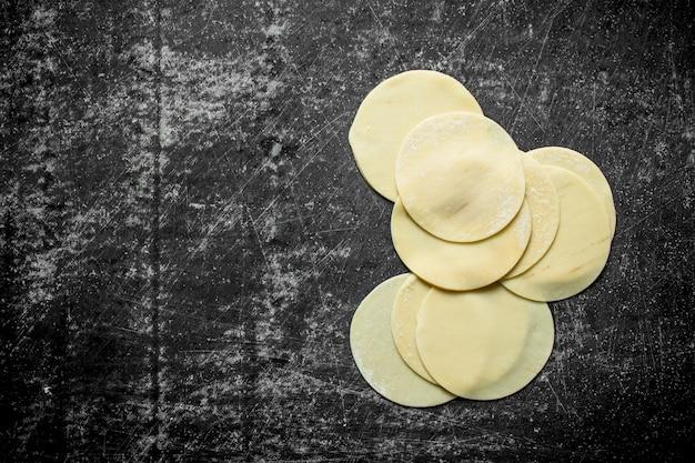 Gnocco crudo. pasta rotonda stesa per gnocchi sul tavolo rustico scuro