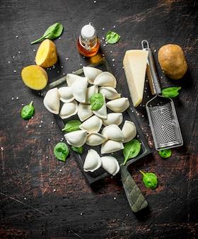 Gnocco crudo con patate, parmigiano e spinaci sul tavolo rustico scuro