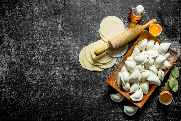 Gnocco crudo con pasta stesa per gnocchi fatti in casa sul tavolo di legno scuro