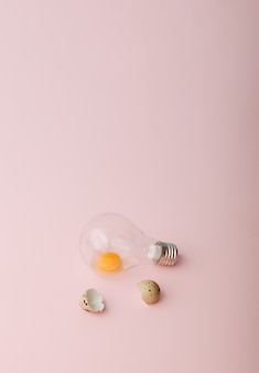 Un uovo crudo in una lampadina e conchiglie accanto ad esso pasqua concetto minimo sfondo rosa