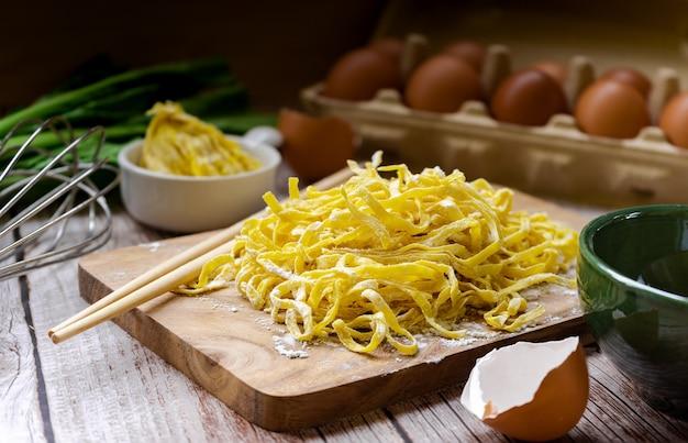 Tagliatelle all'uovo crude a base di farina di uova e polvere - ingredienti artigianali tailandesi per maiale rosso arrosto con pasta