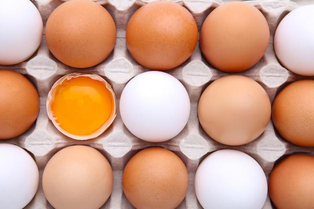 Uova crude in cartone per fondo. l'uovo di pollo è mezzo rotto tra le altre uova