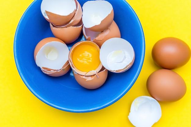 Uova crude, tuorlo e guscio in un piatto blu su una superficie gialla. cucinare un piatto di uova