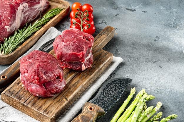 Filet mignon crudo o bistecche con set di erbe e spezie, sul tagliere di legno, sul tavolo di pietra grigia