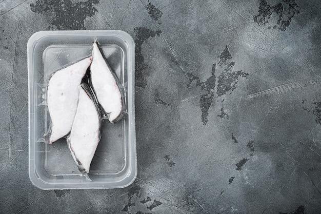 Set sottovuoto ermetico di halibut congelato a filetti crudi, su tavolo in pietra grigia, vista dall'alto piatta