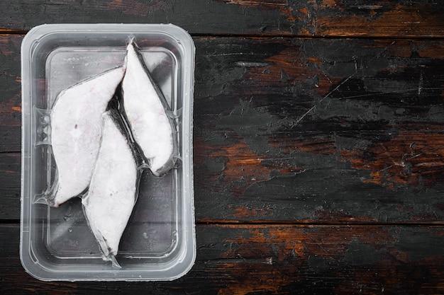 Filetti crudi congelati halibut set sottovuoto ermetico, su vecchio tavolo di legno scuro, vista dall'alto piatta