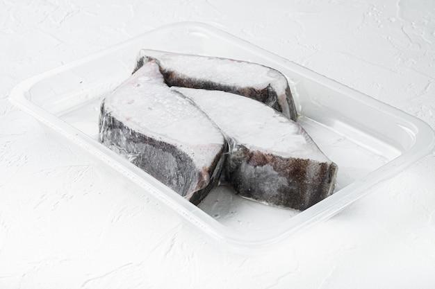 Set sottovuoto ermetico di filetti crudi di halibut congelato, su tavola di pietra bianca