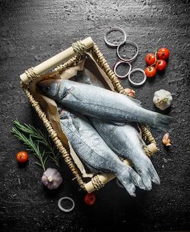 Pesce crudo in un cesto con pomodori, aglio e anelli di cipolla sulla tavola rustica nera.