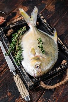 Pesce crudo butterfish o pompano con erbe aromatiche in un vassoio di legno. fondo in legno scuro. vista dall'alto.