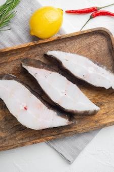 Set di taglio di pesce crudo, con ingredienti ed erbe di rosmarino, su sfondo di tavolo in pietra bianca, vista dall'alto piatta