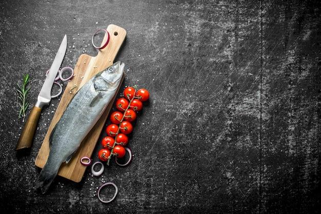 Pesce crudo sul tagliere con coltello, pomodorini e anelli di cipolla. su sfondo nero rustico