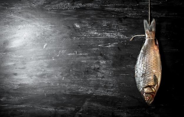 Pesce crudo che appende su una corda. su uno sfondo di legno nero.