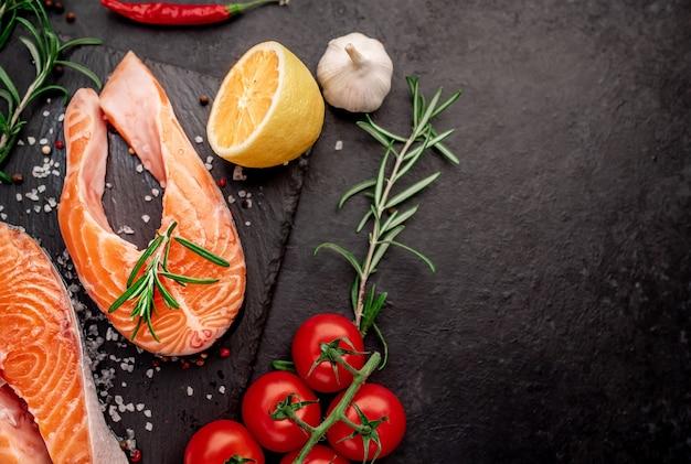 Trancio di salmone di pesce crudo con limone e rosmarino sul tavolo di pietra