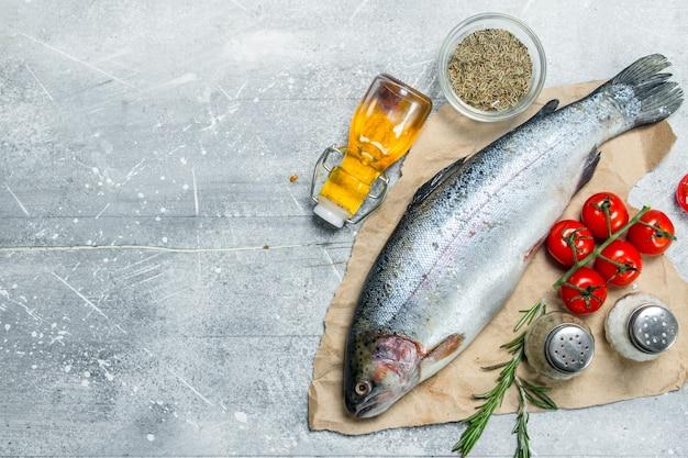 Salmone di pesce crudo con pomodori, spezie e rosmarino. su un rustico.