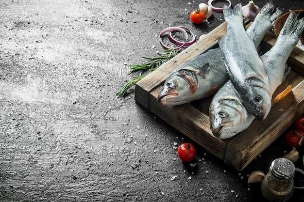 Spigola di pesce crudo su vassoio con rosmarino. su sfondo nero rustico