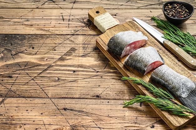Carpa d'argento pesce crudo affettato in bistecche. fondo in legno. vista dall'alto. copia spazio.