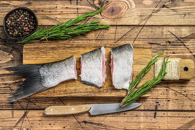 Carpa d'argento pesce crudo affettato in bistecche. fondo in legno. vista dall'alto.