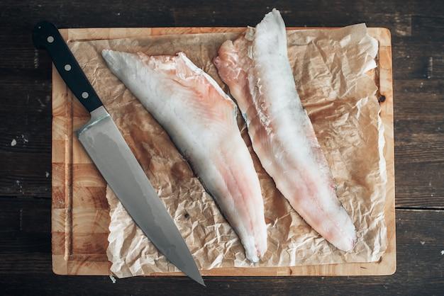 Fette di pesce crudo e coltello sul tagliere ricoperto di carta pergamena, vista dall'alto