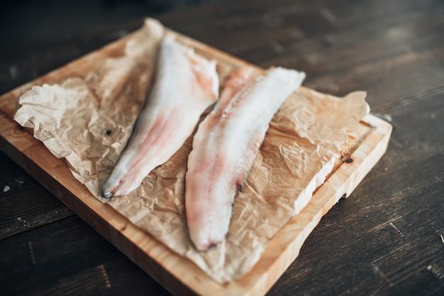 Fette di pesce crudo, coltello sul tagliere, vista dall'alto