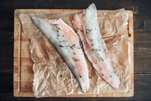 Fette di pesce crudo con spezie sul tagliere ricoperto di carta pergamena, vista dall'alto