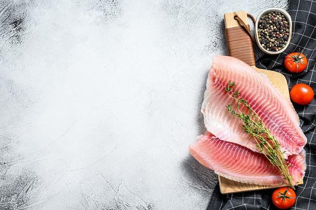 Tilapia di pesce crudo sul tagliere. sfondo grigio. vista dall'alto. copia spazio.