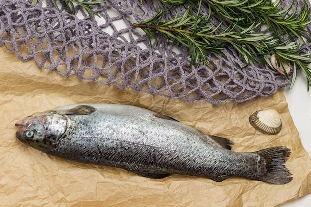 Trota di pesce crudo su carta. rametti di rosmarino sul sacchetto a rete. lay piatto