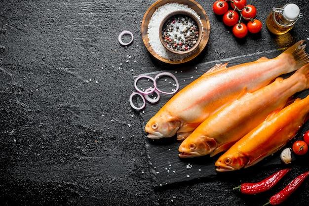 Trota di pesce crudo con peperoncino, pomodorini e spezie. su fondo rustico scuro