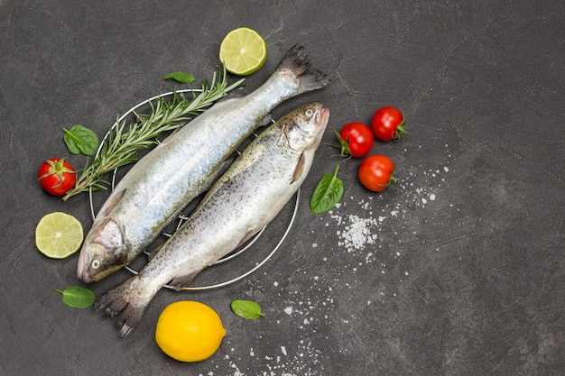 Trota di pesce crudo con rametti di rosmarino, spicchi di limone e pomodori. lay piatto. copia spazio