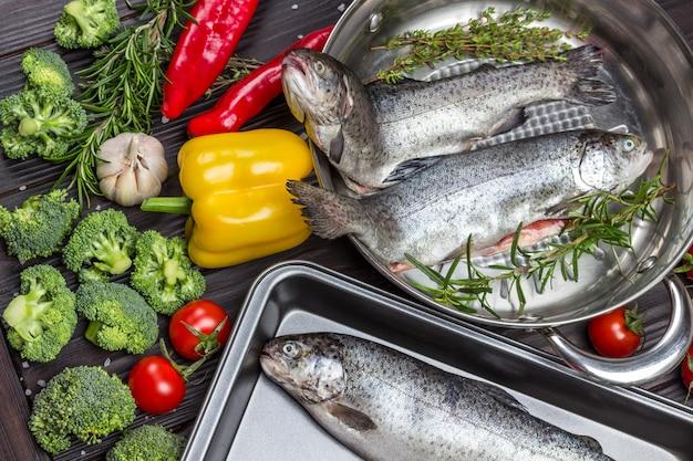 Trota di pesce crudo con verdure in padella e vassoio in metallo. cavolfiore, ceci, rosmarino e limone, funghi e paprika. lay piatto