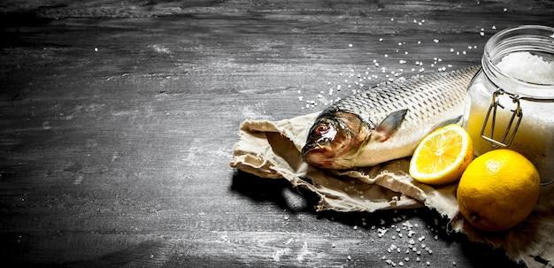 Pesce crudo con sale e limone. su uno sfondo di legno nero.