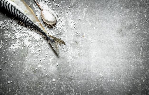 Pesce crudo con un cucchiaio di sale sul tavolo di pietra.