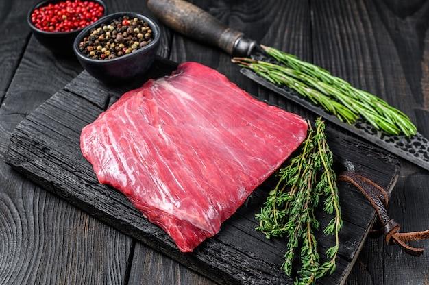 Bistecca di carne di manzo crudo o bavette su un tagliere di legno