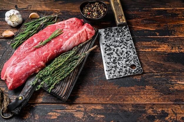 Bistecca di carne di manzo cruda su un tagliere con mannaia