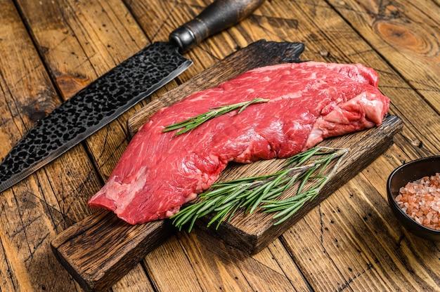 Bistecca di carne di manzo crudo fianco su un tagliere con coltello