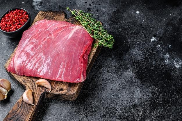 Bistecca di carne di manzo crudo o lembo su un tagliere di legno