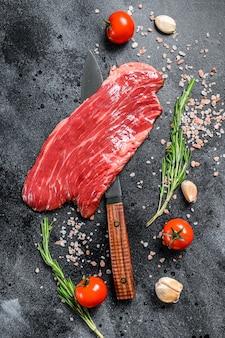 Bistecca di fianco cruda black angus. carne fresca di manzo in marmo. sfondo nero. vista dall'alto.
