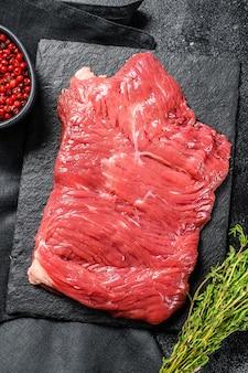 Bistecca di fianco cruda, carne marmorizzata. sfondo nero. vista dall'alto. copia spazio.