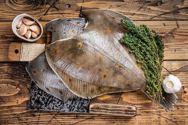 Pesce piatto della passera pianuzza crudo sul bordo del macellaio con la mannaia. fondo in legno. vista dall'alto.