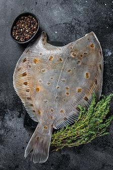 Pesce crudo passera pianuzza su tavola di marmo con timo. sfondo nero. vista dall'alto.