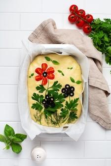 Focaccia cruda decorata creativamente con verdure su carta forno. focaccia ai fiori fatta in casa. pasta madre. pane italiano decorato. vista dall'alto