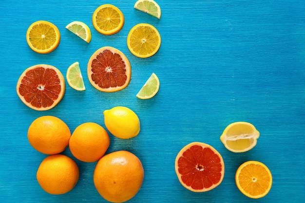Affettamento di cibo crudo e agrumi interi arancia limone pompelmo vista dall'alto frutti o