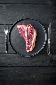 Set di bistecca con l'osso di manzo crudo fresco e secco invecchiato, su piatto, su tavolo di legno nero