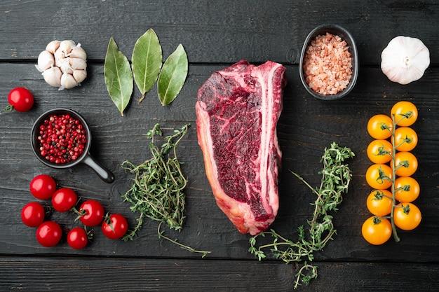 Carne cruda fresca marmorizzata black angus club di bistecca e ingredienti su tavola di legno nero