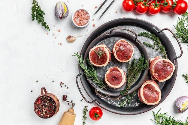 Carne fresca marmorizzata cruda filet mignon di bistecca. bistecche di filetto di manzo avvolte in pancetta servite su un vecchio vassoio di carne su uno sfondo chiaro. vista dall'alto.