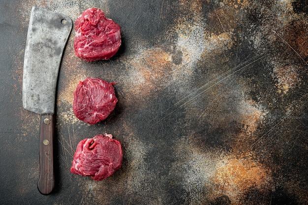 Set mignon di filetto di bistecca di carne marmorizzata fresca cruda e vecchio coltello da macellaio, sul vecchio rustico scuro
