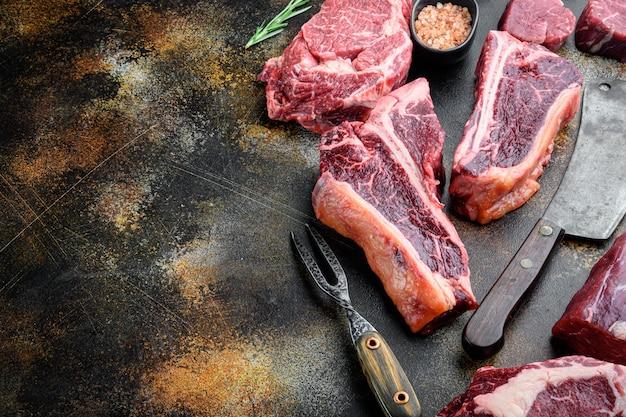 Bistecca di carne cruda fresca marmorizzata, set di condimenti, tomahawk, t bone, bistecca, costata di manzo e filetto